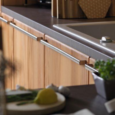 Küche Rondo in Kernbuche mit Griffstangenvariante oval in Edelstahl-Finish