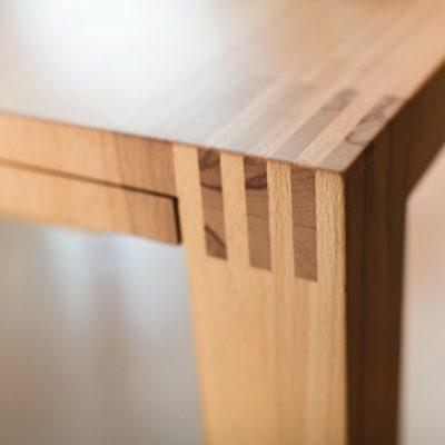 Sichtbar verzapfte Tischbeine mit einem über die Tischkanten laufenden Holzbild