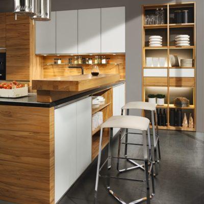 Küchelinee in weiss mit Küchenblock und hochgesetzter Thekenlpatte davor Hocker lux