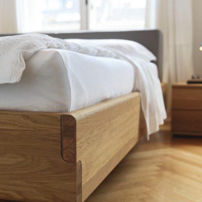 Bett nox mit gegenläufig gerundeten Bettseiten, die sich an den Ecken zu einer eleganten S-Linie vereinen