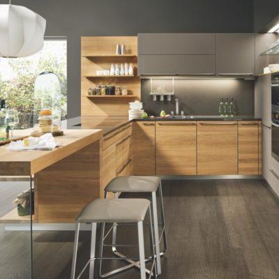 Küche linee in Eiche mit 79 mm starker Anbautischplatte davor Hocker lux
