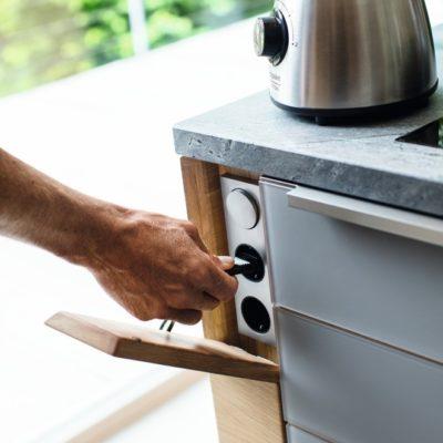 Küche linee mit verdeckten Steckdosen und Schalter hinter Eichenholzfrontklappe