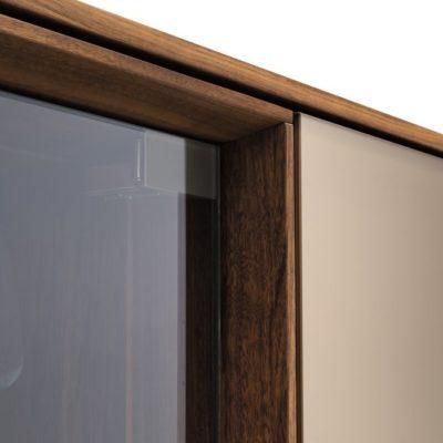 Anrichte filigno in Nussbaum und Farbglas Bronze links daneben das Gestaltungselement mit Klarglastür